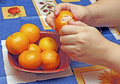 Woman cleans tangerines Royalty Free Stock Photos
