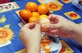 Woman cleans tangerines Stock Photography