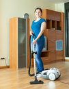 Woman cleans with vacuum cleaner full length shot of at home Royalty Free Stock Photo