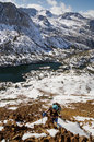 Woman climbing chocolate peak up in the sierra nevada mountains with long lake below her Stock Photos