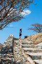 Woman climbing stairs to desert fortress