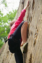 Woman climbing up brick wall female rock climber a Royalty Free Stock Image
