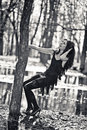 Woman clings to a tree. Black and white photo Royalty Free Stock Photo