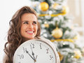 Woman with clock looking on copy space in frontof christmas tree Royalty Free Stock Photo