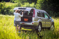 Woman close the suv in countryside holding baggage nissan x trail meadow Stock Image