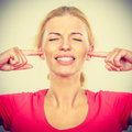 Woman closing ears with fingers, big noise. Royalty Free Stock Photo