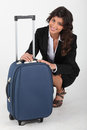 Woman closing her luggage Royalty Free Stock Image
