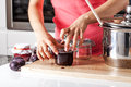 Woman closing the jars with plum jam Royalty Free Stock Photos