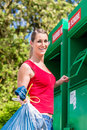 Woman at clothes recycling skip happy Royalty Free Stock Images