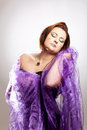 Woman with clown make up as a made nestles in a purple blanket Royalty Free Stock Photos