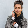 Woman in coat holding phone paying attention winter making a call outdoors Stock Images