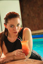 Woman with cocktail drink at swimming pool edge attractive seductive in black dress relaxing poolside young sensual girl tropical Royalty Free Stock Images