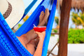 Woman with cocktail relaxed in hammock on beach Royalty Free Stock Photo