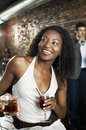 Woman with cocktail sitting in bar cheerful african american women Royalty Free Stock Photography