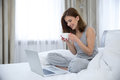 Woman with coffe and laptop sitting on the bed portrait of a happy at home Stock Images