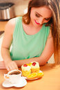 Woman with coffee and cake in kitchen gluttony cup of delicious gourmet sweet cream cupcake orange glutton girl sitting hot Stock Images