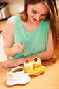 Woman with coffee and cake in kitchen gluttony cup of forking delicious gourmet sweet cream cupcake orange glutton girl sitting Royalty Free Stock Photos
