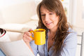 Woman with coffee cup and newspaper beautiful young reading at home Royalty Free Stock Photography