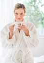 Woman with coffee cup sitting on massage table at spa portrait of beautiful young health Stock Image
