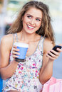 Woman with coffee and mobile phone young outdoors Royalty Free Stock Photo