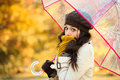 Woman in cold autumn with umbrella shivering and holding transparent brunette fashion girl covering her mouth scarf outside Royalty Free Stock Photos