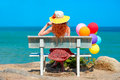 Woman with colored balloons sitting on a bench looking at the sea Royalty Free Stock Photo