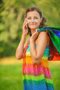 Woman in colorful dress of said cellular phone beautiful young shop hands against green summer park Royalty Free Stock Images