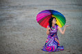 Woman with colorful umbrella under the rain