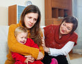 Woman comforting adult daughter with baby young mother has trouble mature women at home Stock Image