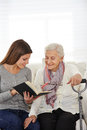 Woman in community service reading young women books to senior citizens Royalty Free Stock Photography