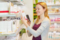 Woman comparing prices with smartphone in drugstore youn her department of a supermarket Royalty Free Stock Image