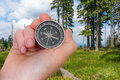 Woman with compass is seeking a right way in forest Royalty Free Stock Photo