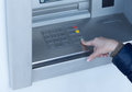 Woman completing a transaction on an atm outside bank as she withdraws cash for personal spending Royalty Free Stock Photo