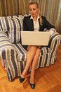 A woman at the computer beautiful young blonde girl in blue jacket blue skirt and white shirt is sitting in an armchair office Royalty Free Stock Photo