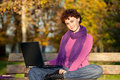 Woman with computer on park bench Stock Photos