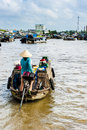 Woman with concal hat driving her machine boat to floating marke market oon mekong river Stock Photo