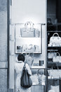 Woman considers bags in a show-window of boutique