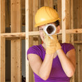 Woman construction worker looking through roll of drawings Royalty Free Stock Photo