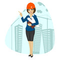 Woman construction worker wearing hard hat holding blueprints and clipboard pointing Royalty Free Stock Photo
