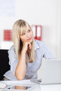 Woman contemplating her business strategy attractive young blond sitting at laptop staring off into space Royalty Free Stock Photo