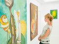 Woman contemplating paintings in art gallery Royalty Free Stock Photo