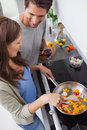 Woman cooking bell pepper while her husband is looking at her Stock Photos