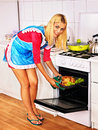 Woman cooking chicken at kitchen young Stock Photography