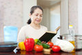 Woman cooking with cookbook in kitchen at home Royalty Free Stock Images