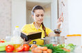 Woman cooking food with book at kitchen Stock Photography