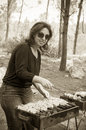 Woman cooking meat on portable barbecue sepia and smile Royalty Free Stock Photos
