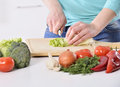Woman cooking in new kitchen making healthy food with vegetables. Royalty Free Stock Photo