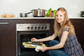 Woman cooking saltwater fish in oven at kitchen smiling and potatoes on sheet pan Stock Image