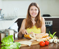 Woman cooking sandwiches with baguette happy Stock Image
