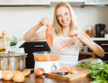 Woman cooking vegetables and salmon with electric steamer happy at home kitchen Stock Photo